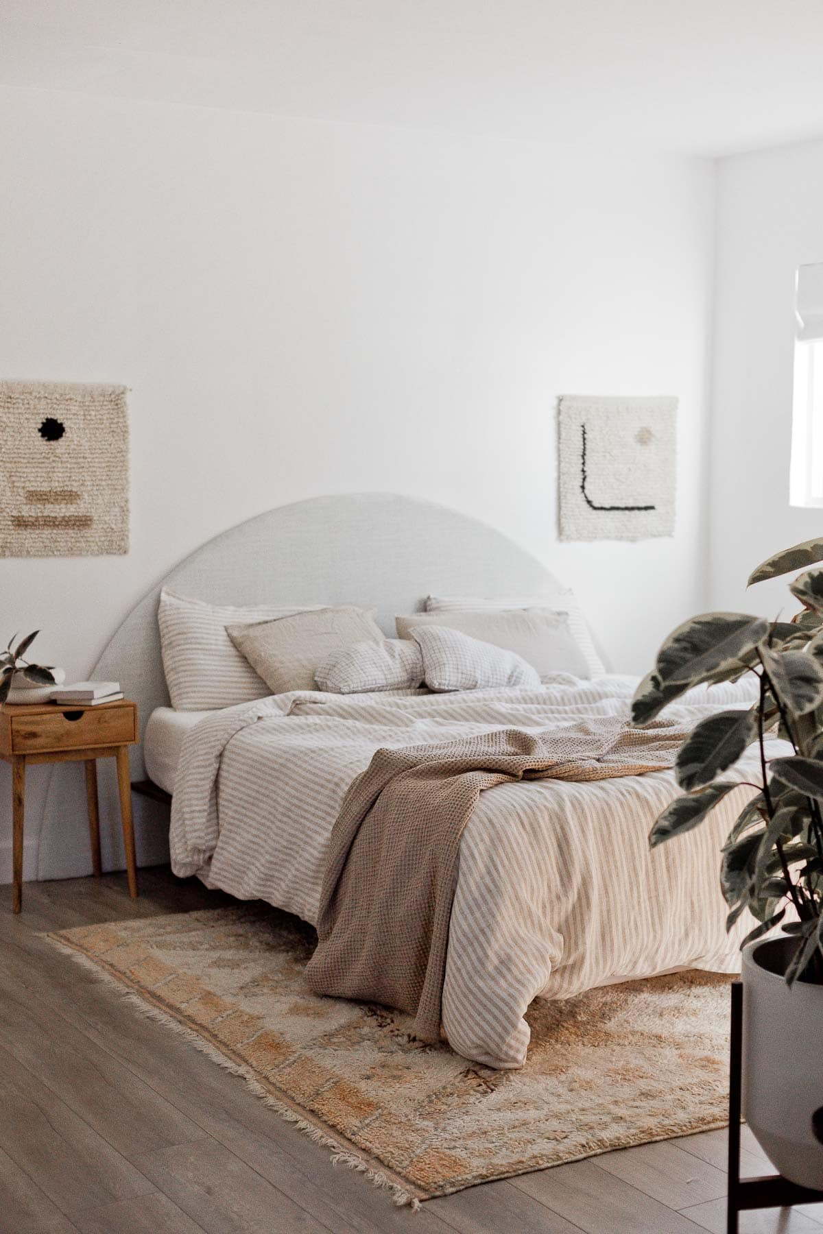 Organic modern bedroom with neutral textiles and unique artwork.