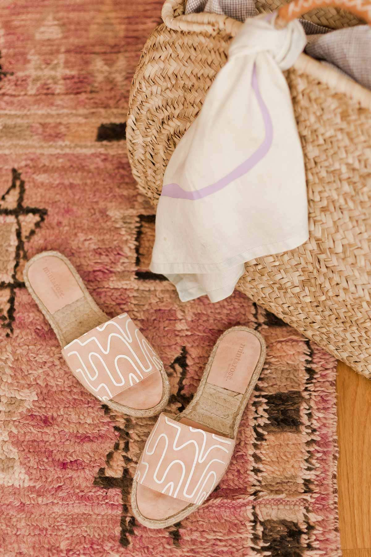 Pink groovy print sandals on a Moroccan rug with a straw bag.