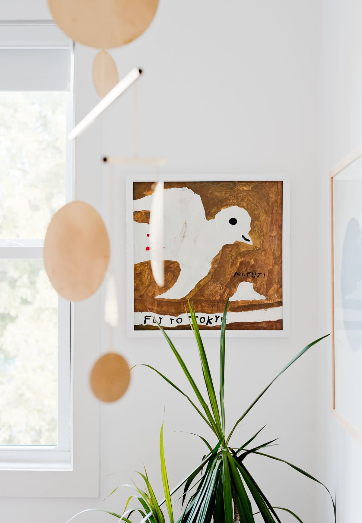Painting of a bird that says 'fly to Tokyo', hanging in a child's nursery.