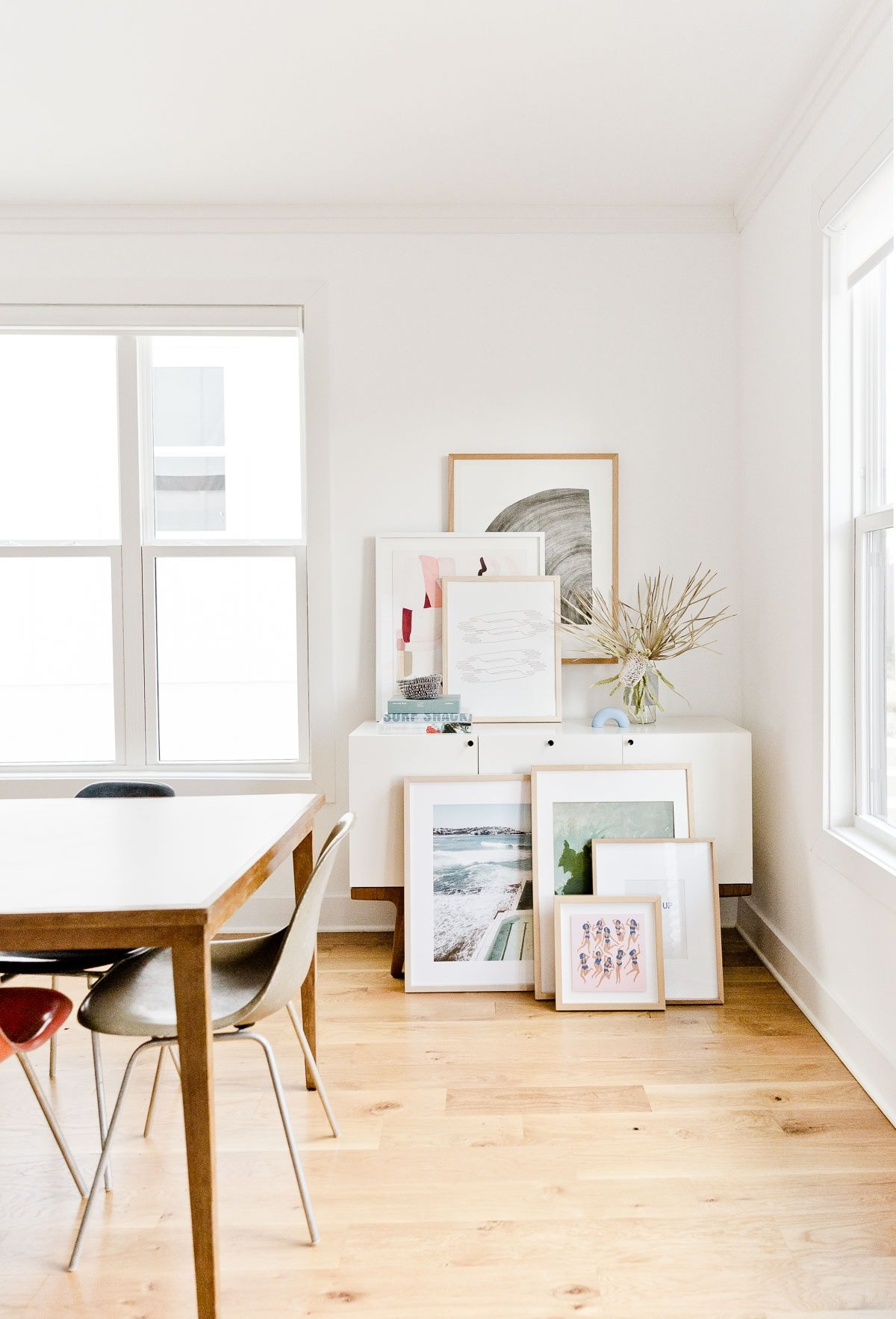 Abstract artwork piled and leaning against a wall in modern home.