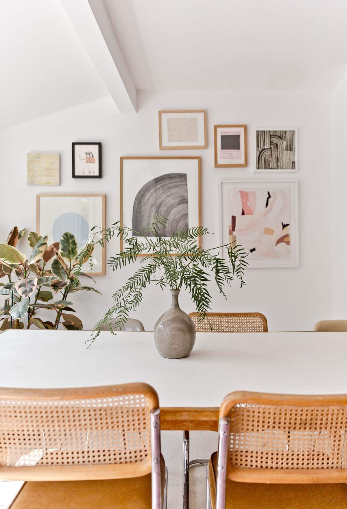 Gallery wall of artwork in modern dining room.