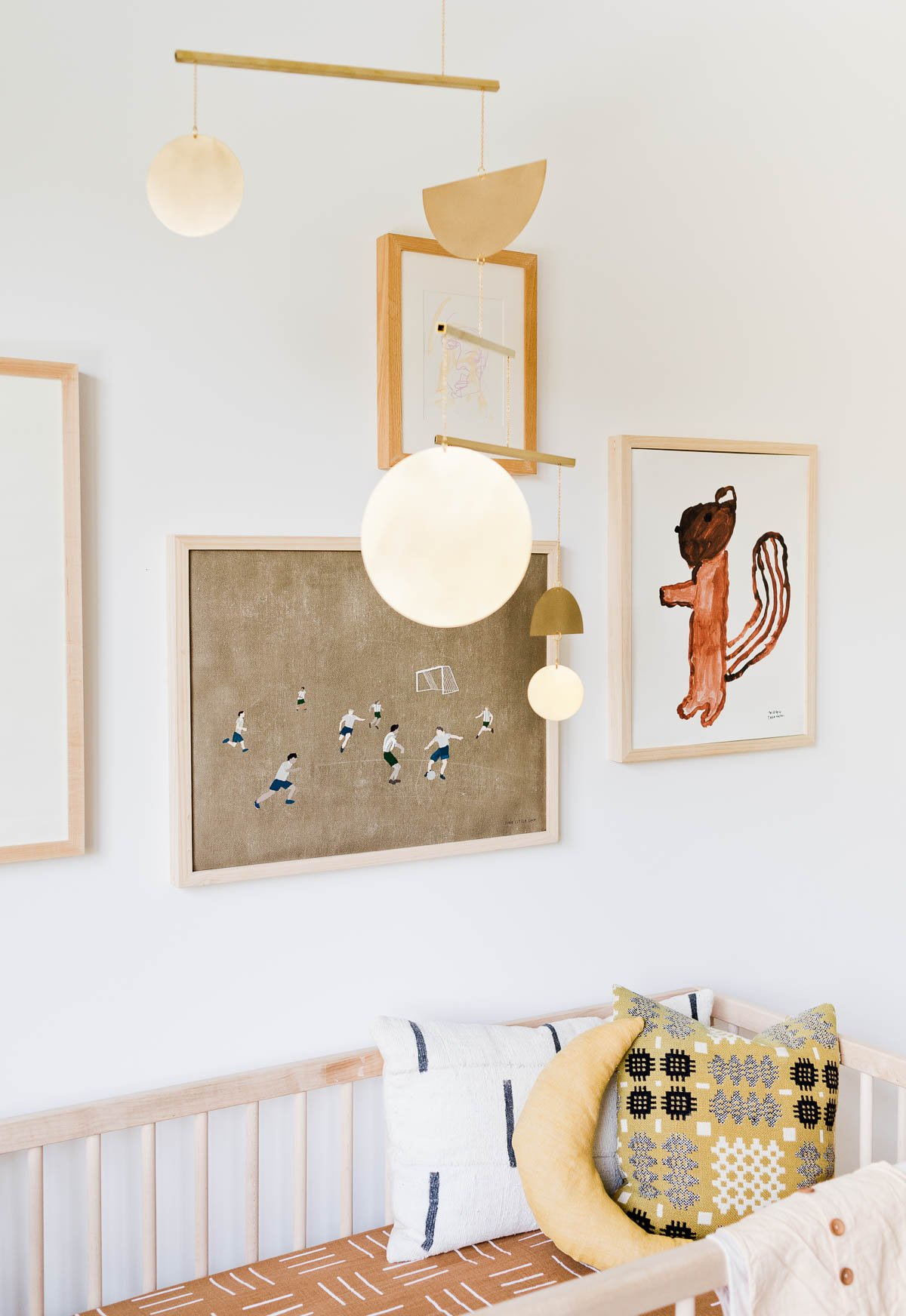 Gallery wall of artwork hanging over modern crib in a neutral nursery.