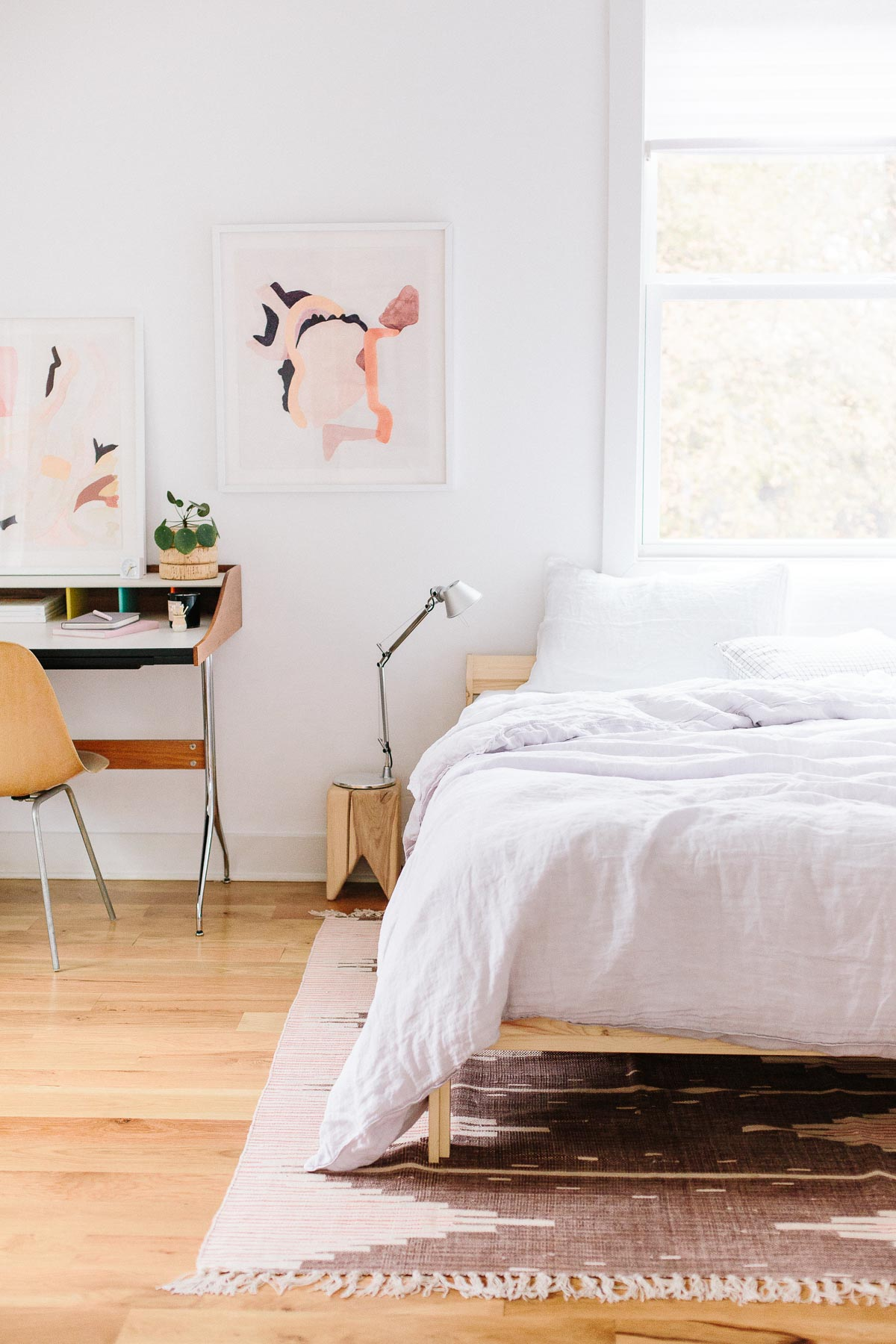 Colorful abstract artwork hanging in a simple, modern bedroom.