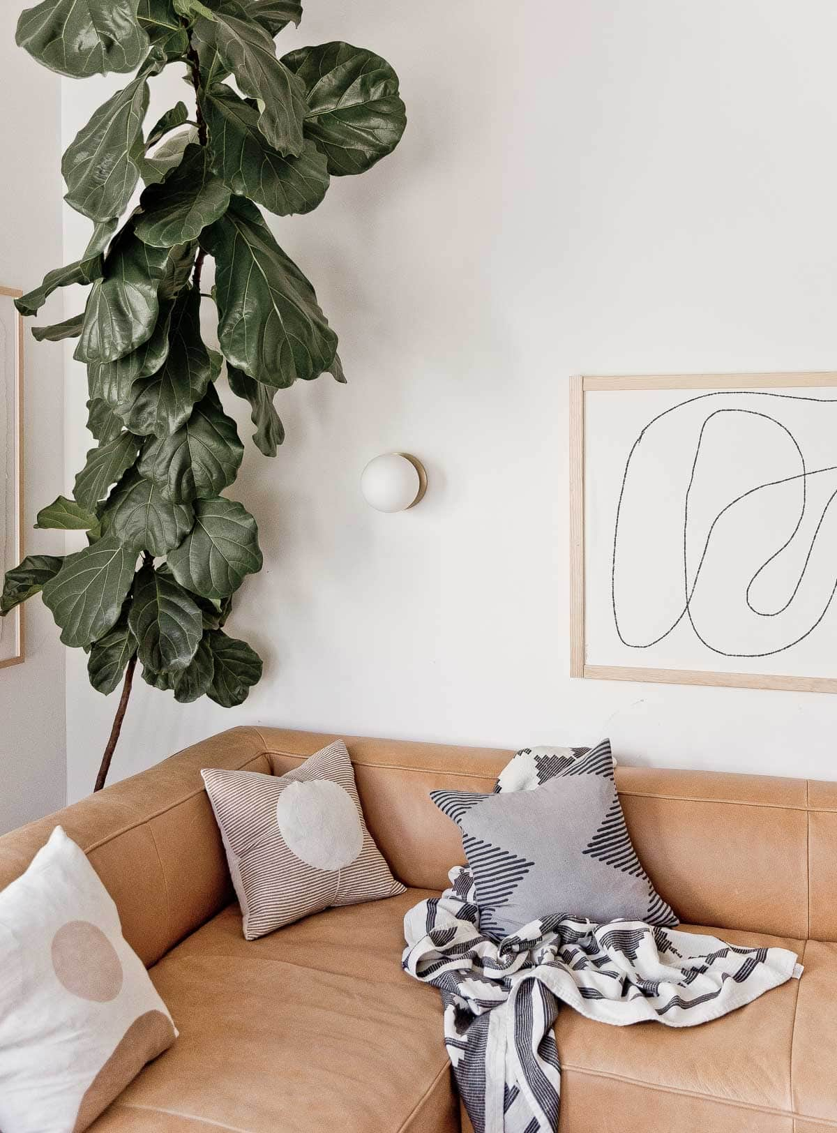 Abstract black and white line drawing hanging in modern living room.