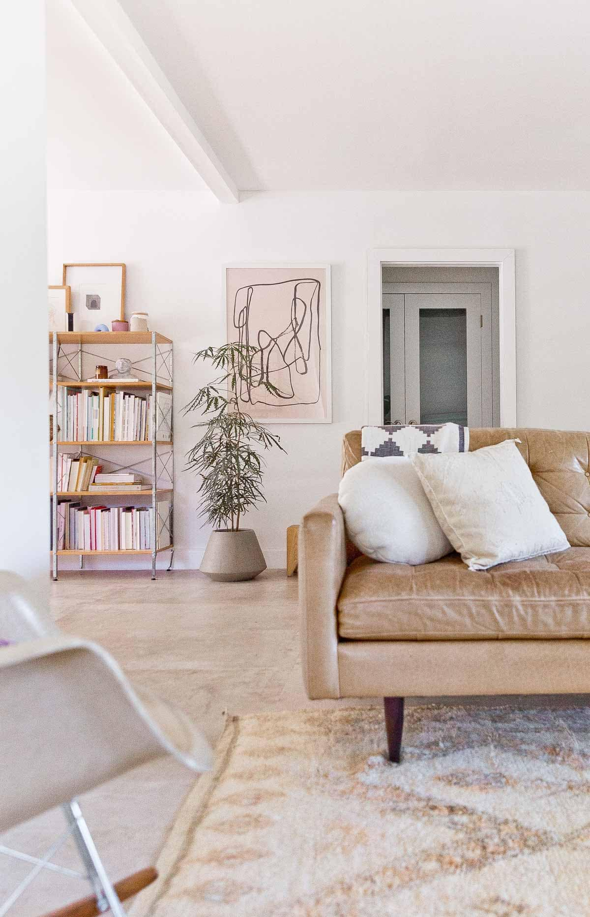 Abstract artwork hanging in organic modern living room with bookshelf.