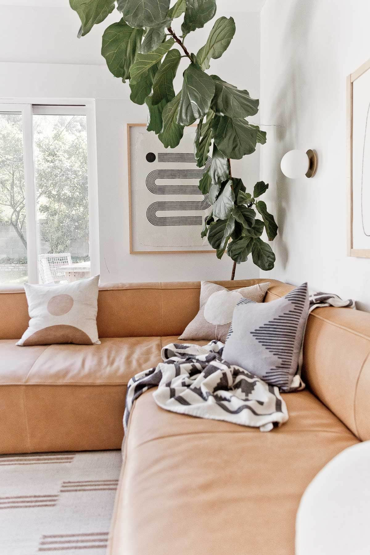 Black and white, modern abstract artwork hanging in a living room with a large fiddle leaf fig tree.