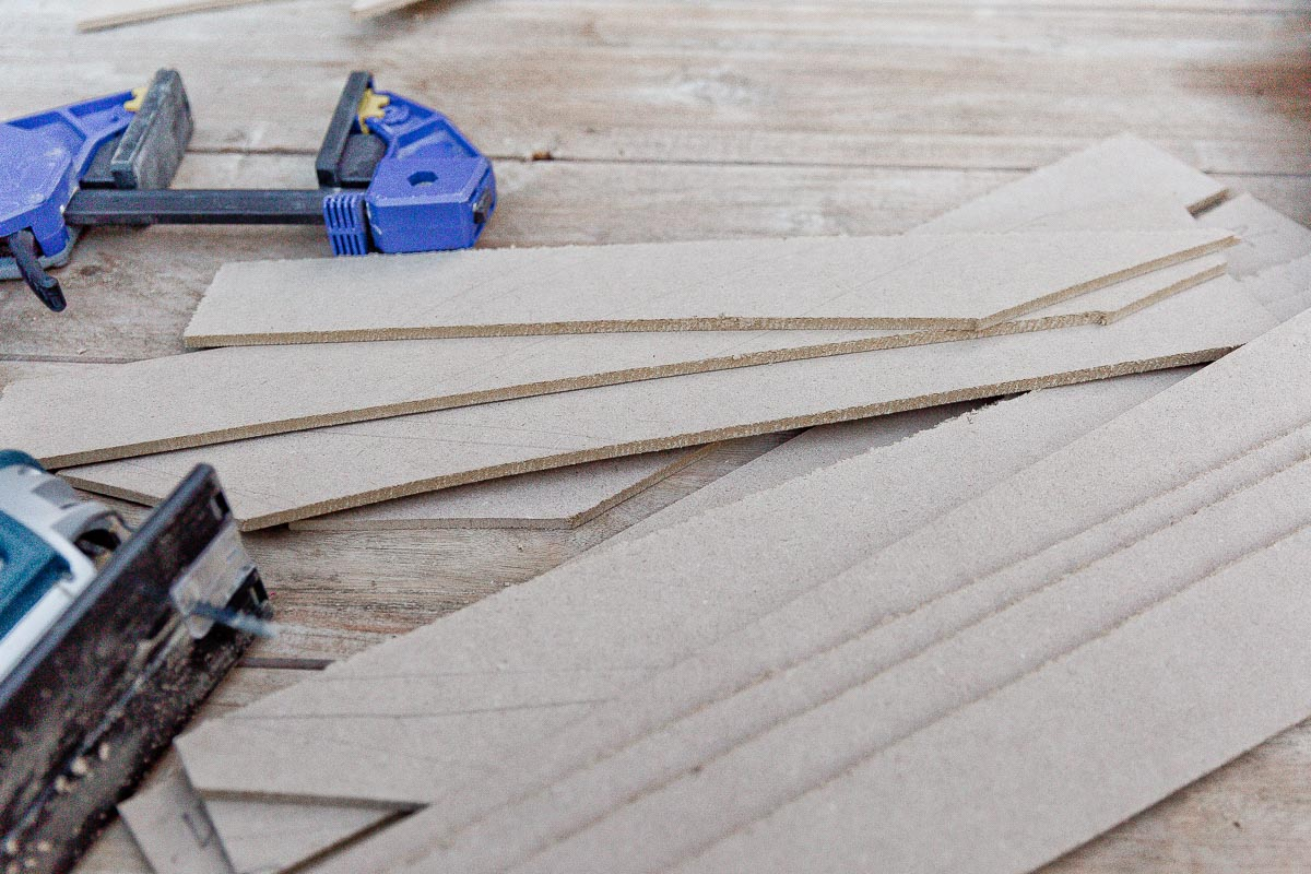 Long strips of MDF panels, cut with a jigsaw, in a pile.