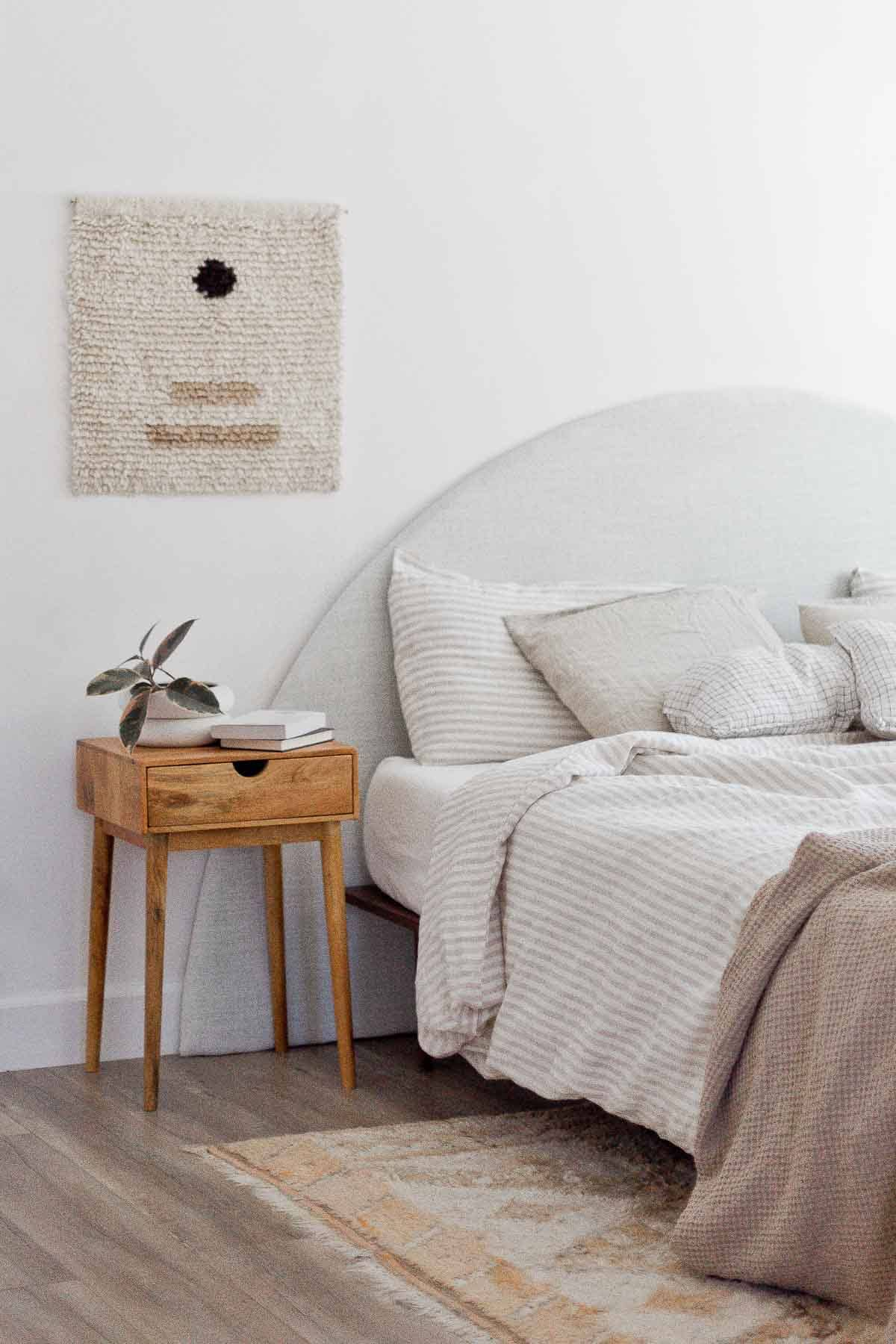 Minimal modern bedroom with neutral bedding and linen half circle headboard.