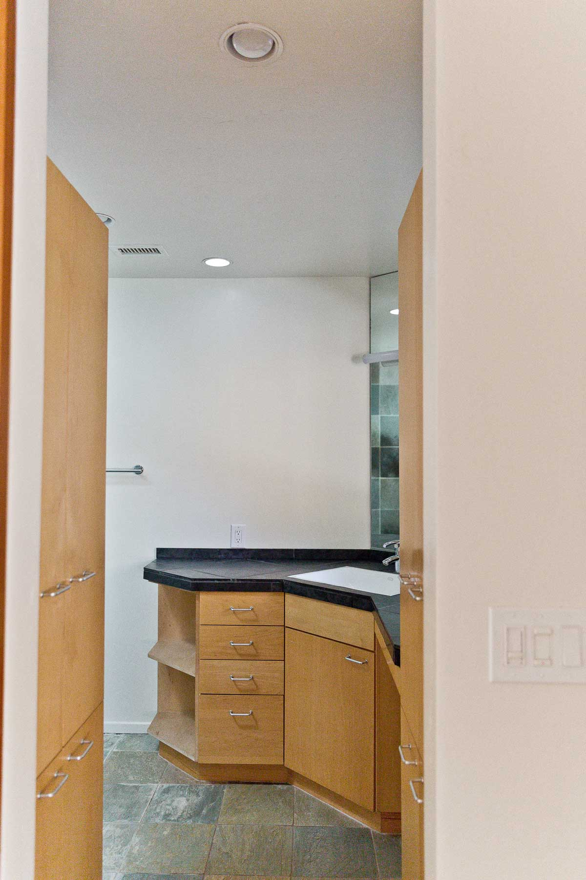 Photo of empty bathroom with wood cabinets and black natural stone counters.