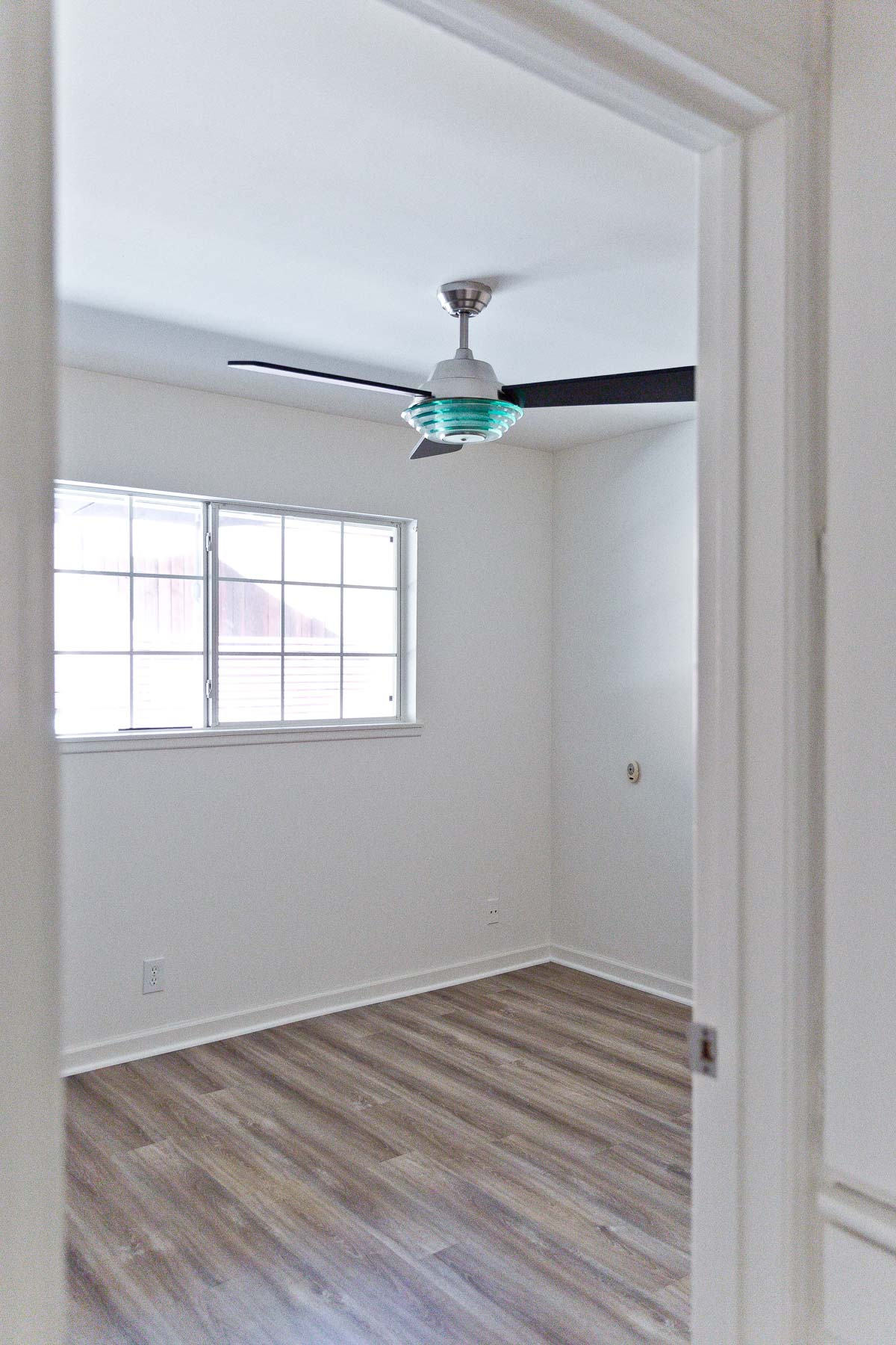 Photo of small, empty bedroom with ceiling fan.