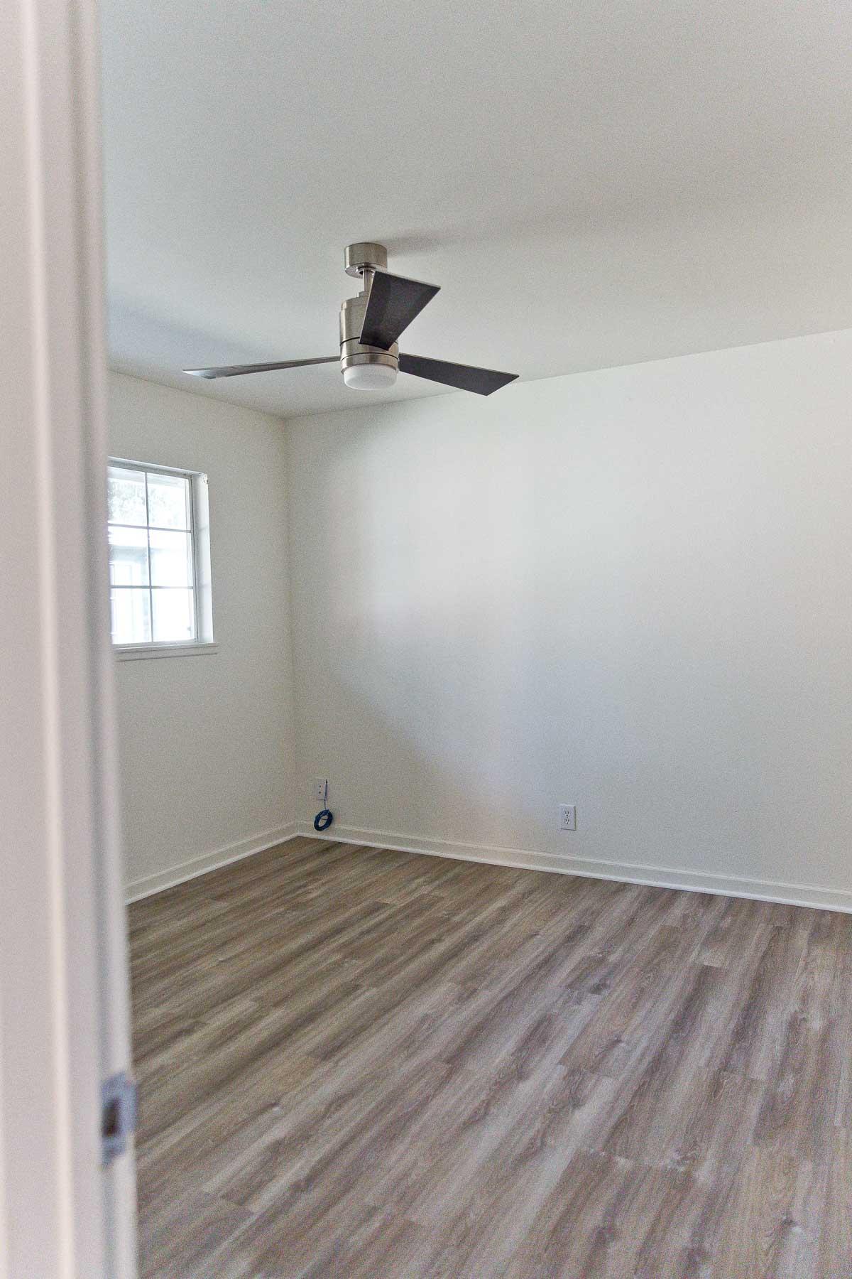 Photo of empty bedroom with modern ceiling fan.