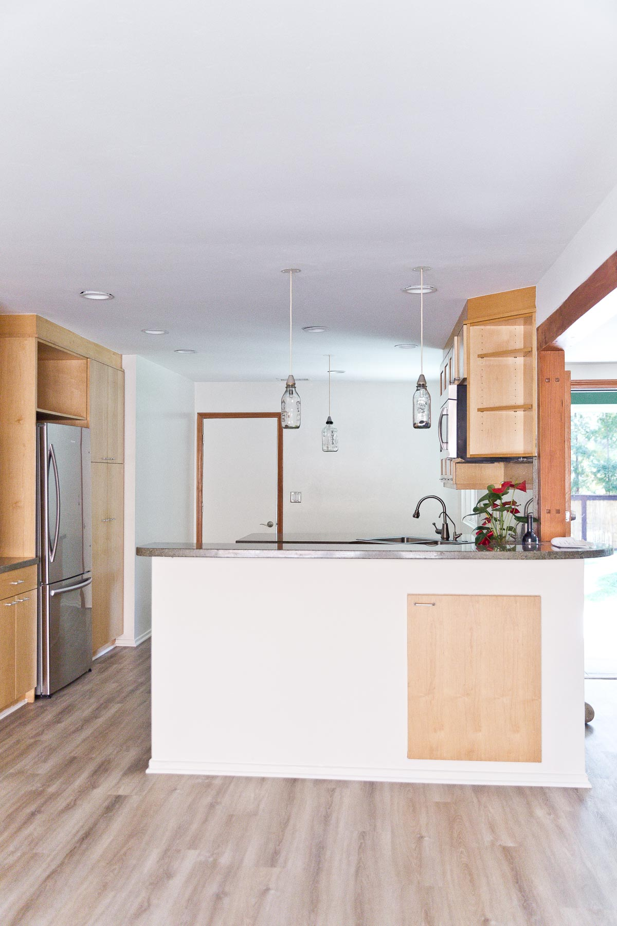 Image of empty kitchen with minimal wood cabinets and white walls.
