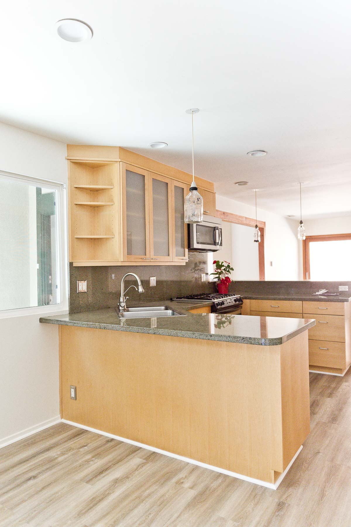 Image of empty kitchen with minimal wood cabinets and green natural stone counters.