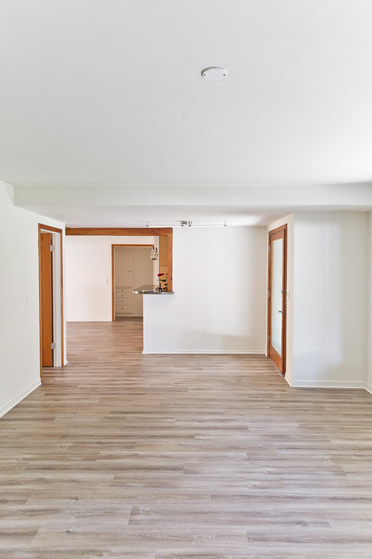 Photo of empty house with white walls and wood floors.