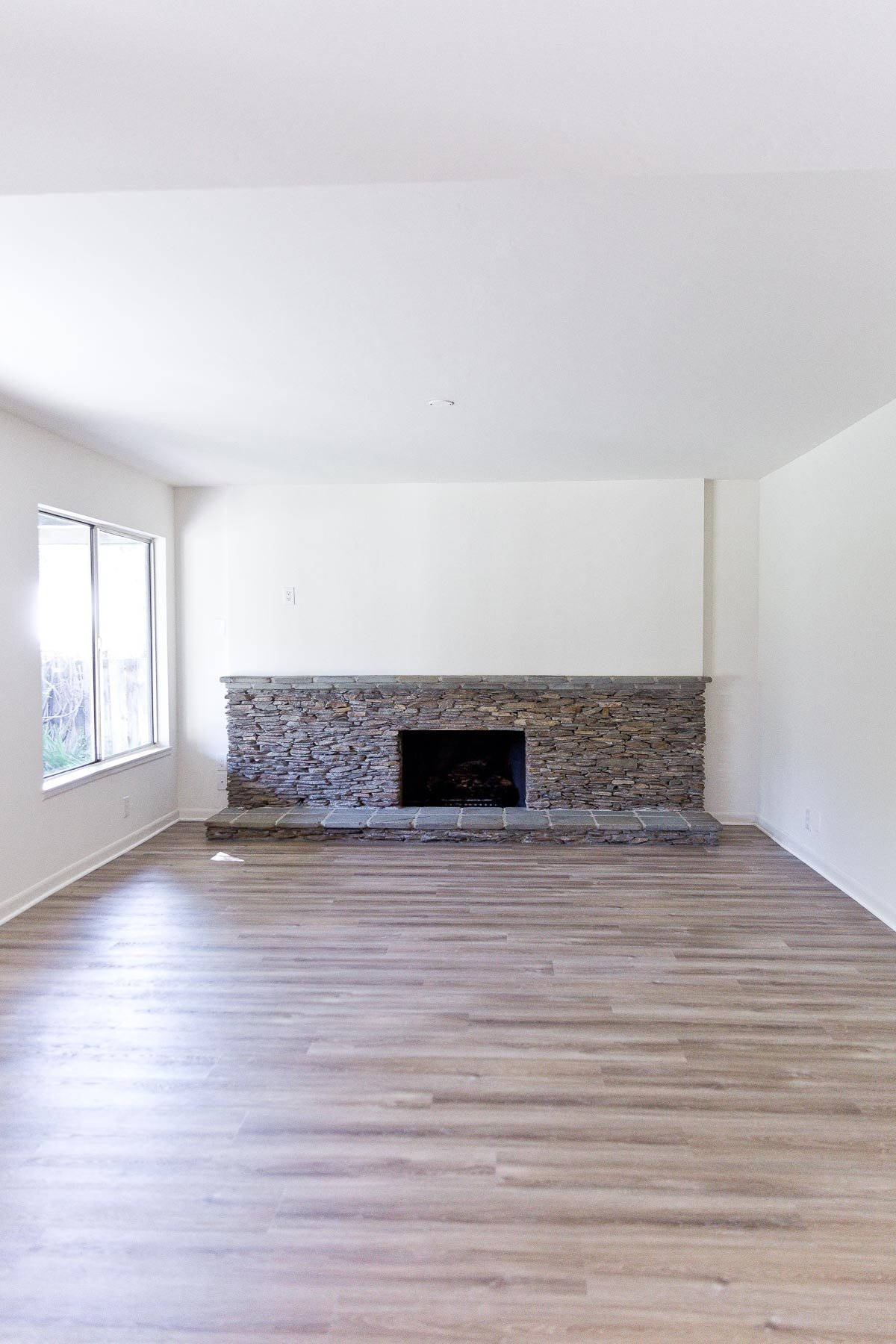 Photo of empty living room with statement ledger rock fireplace.