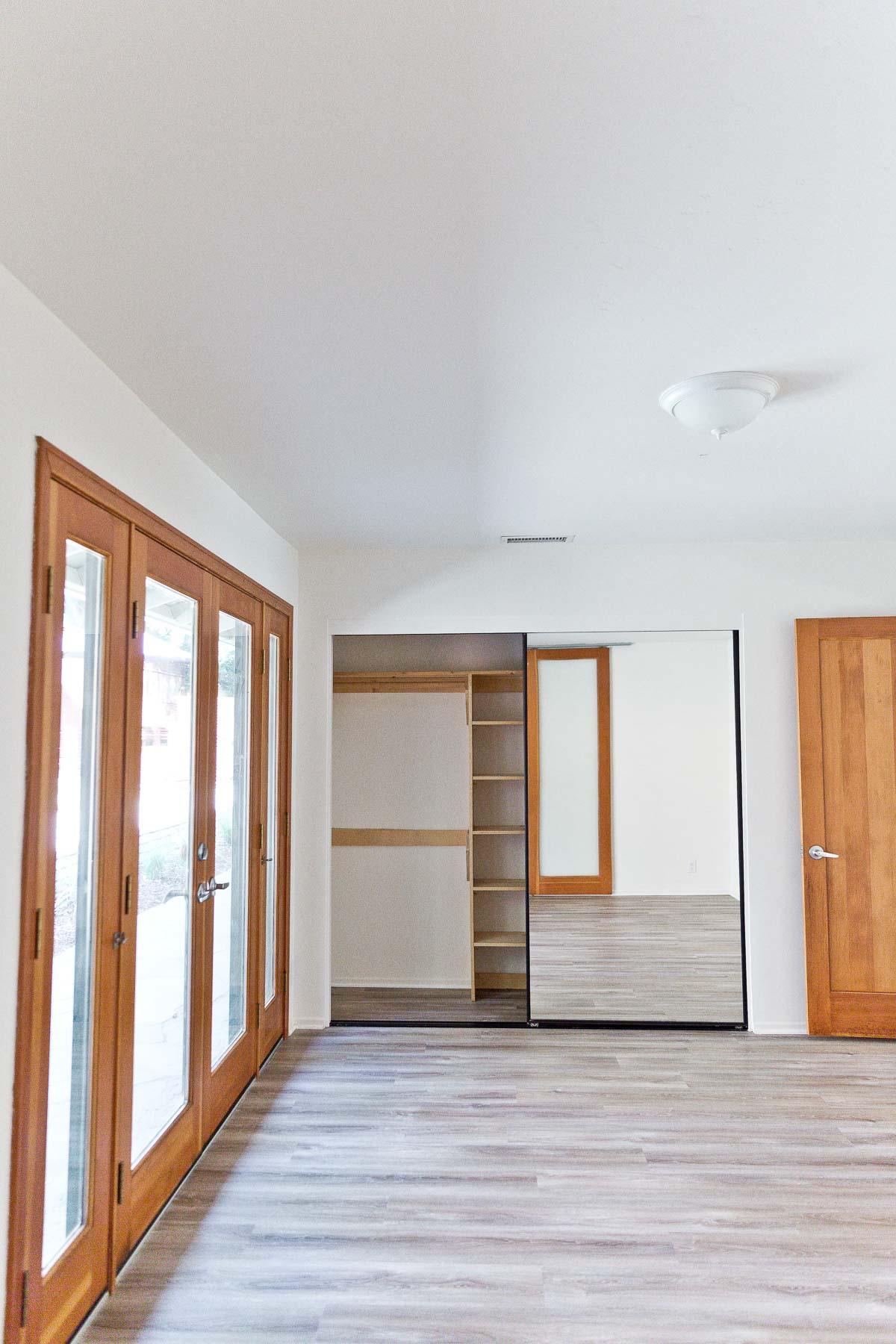 Photo of mirrored sliding doors in empty bedroom space.