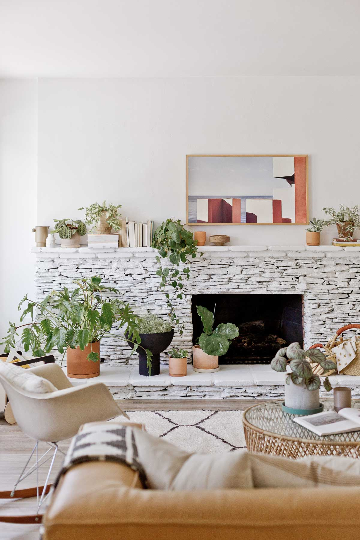 painted white fireplace with many plants and books, iim a living room space