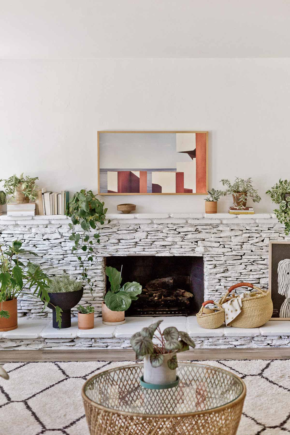 stacked stone fireplace, painted white with plants and organic modern decor