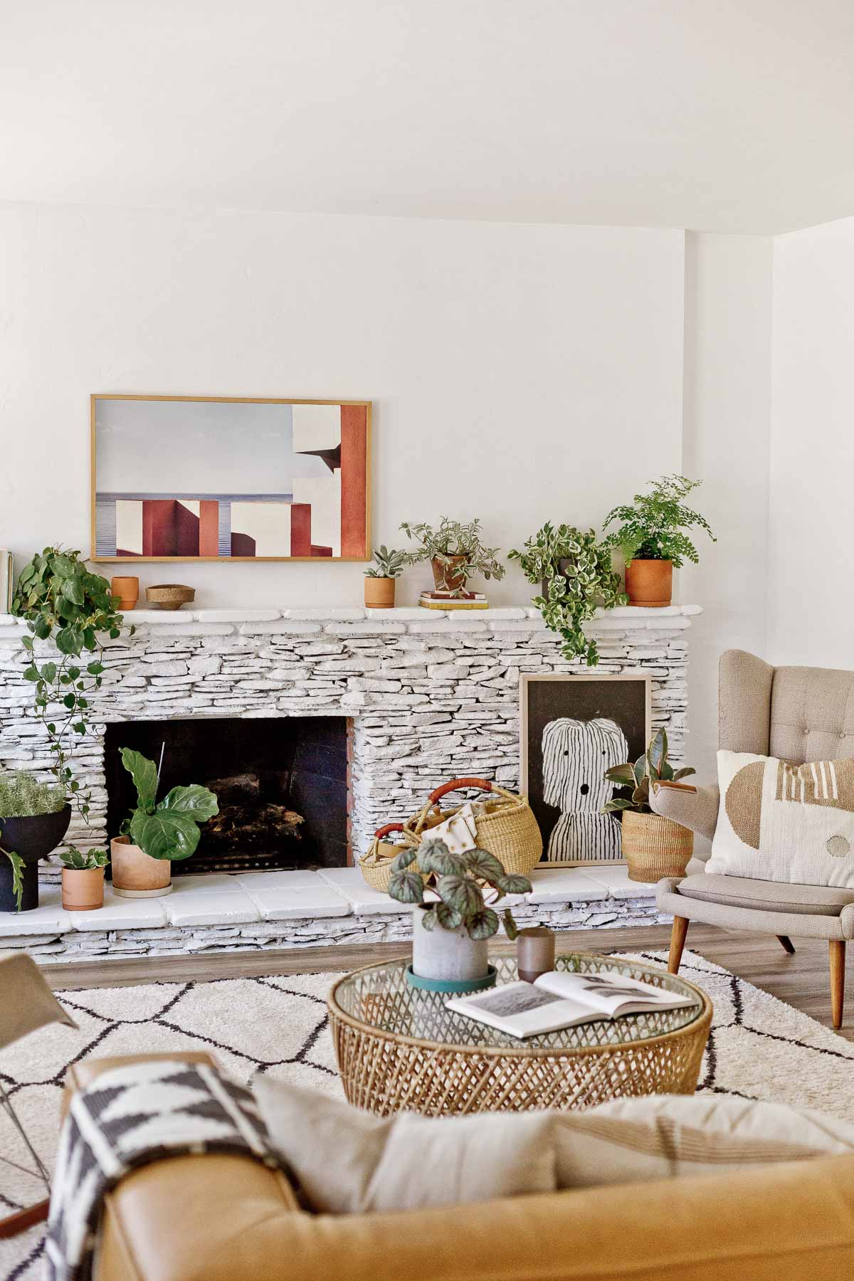 painted white stone fireplace with plants and large neutral artwork