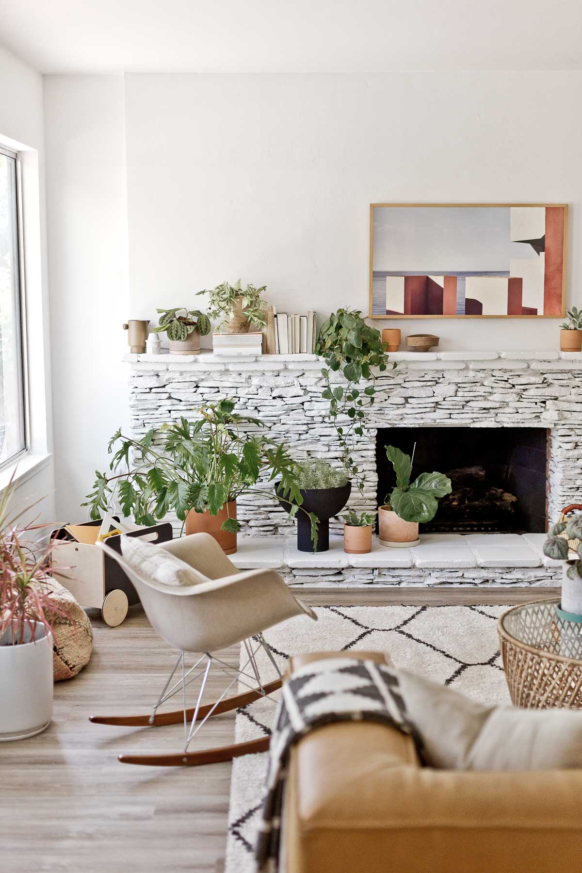 white painted fireplace made of stone with modern rocking chair and large plants throughout the room