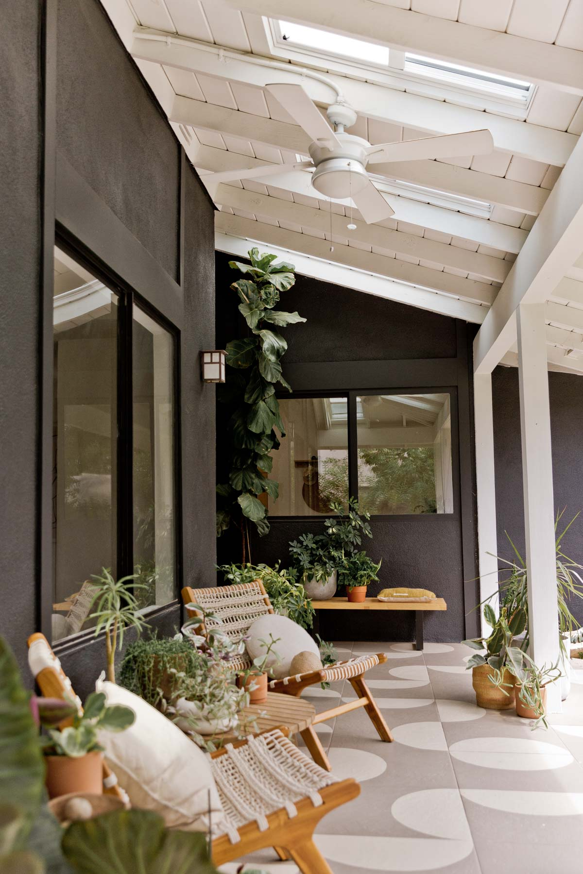 Modern front porch with painted tile floors and black exterior pant.