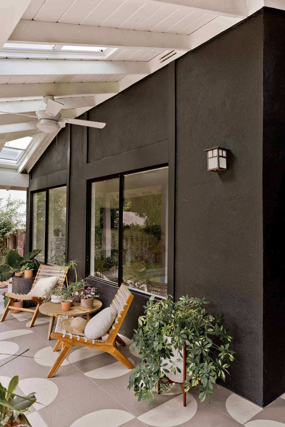 Modern front porch with black exterior and painted pattern tile flooring.