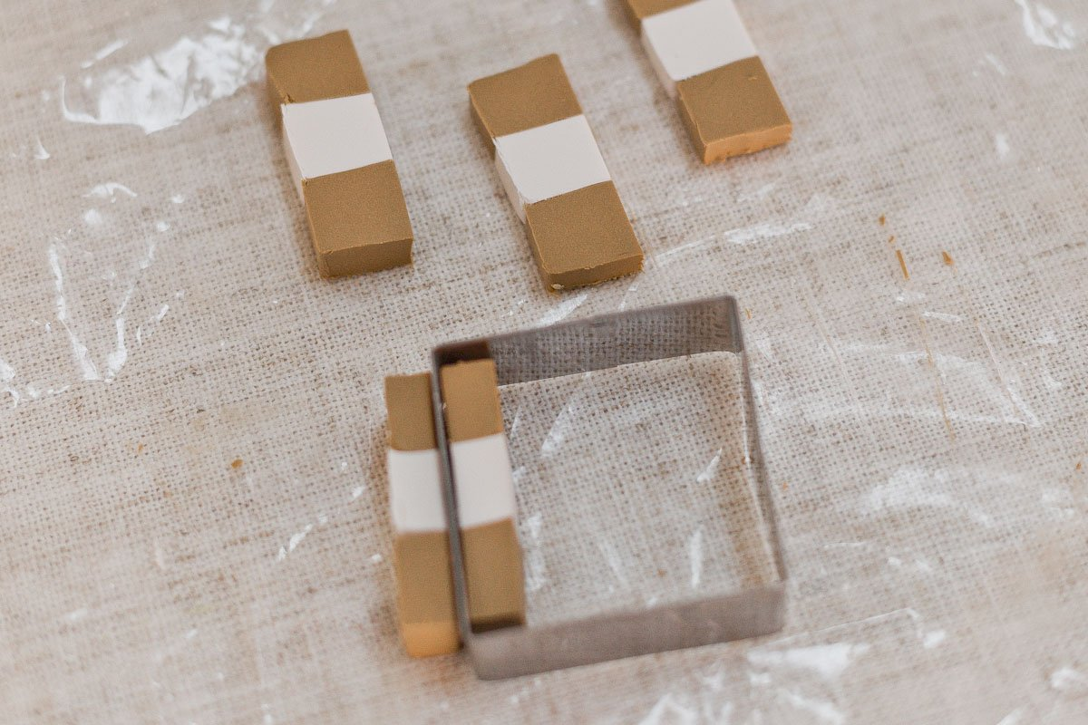 Cutting clay into squares with cookie cutter.