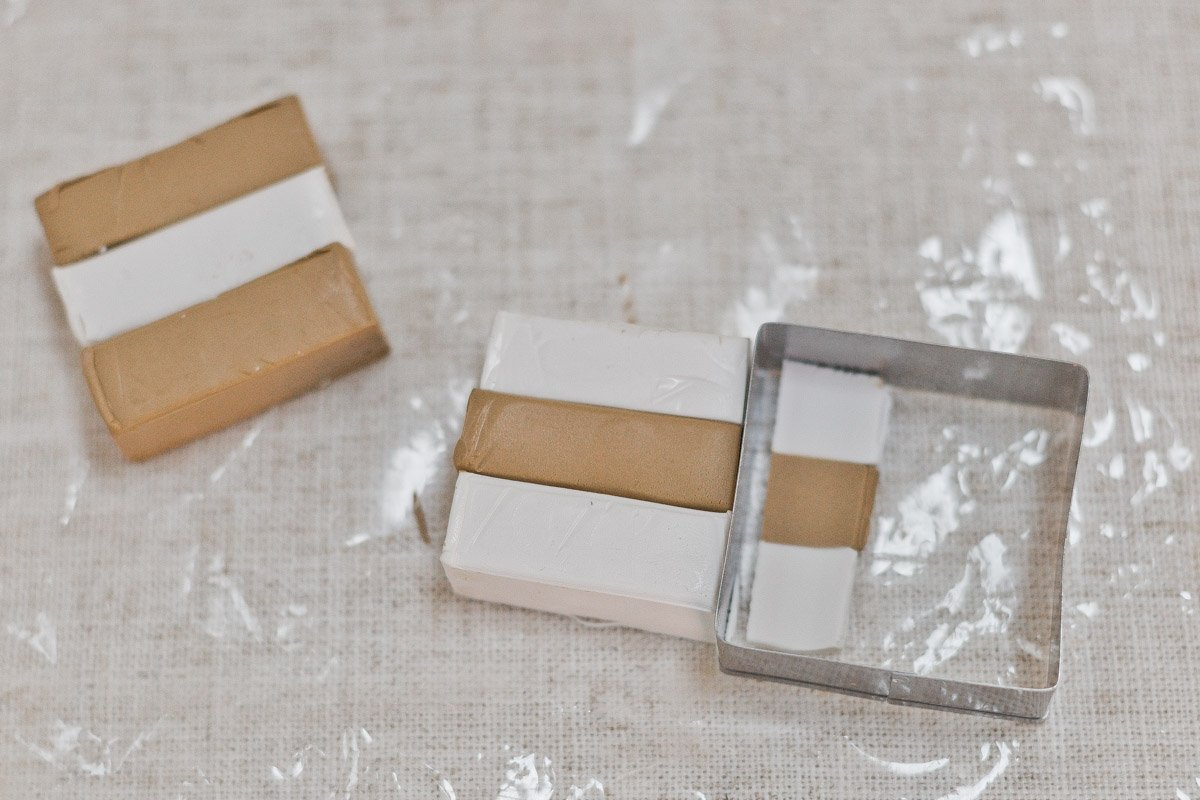 Cutting two colors of oven bake clay with square cutter.