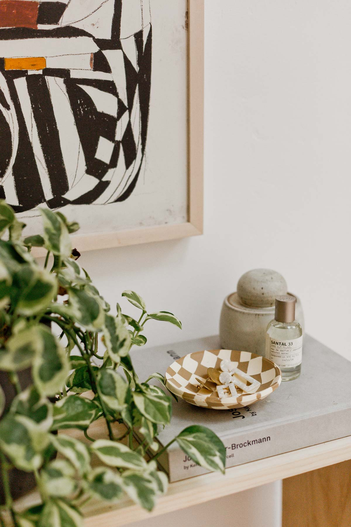 Clay bowl on modern table with plants and abstract artwork.