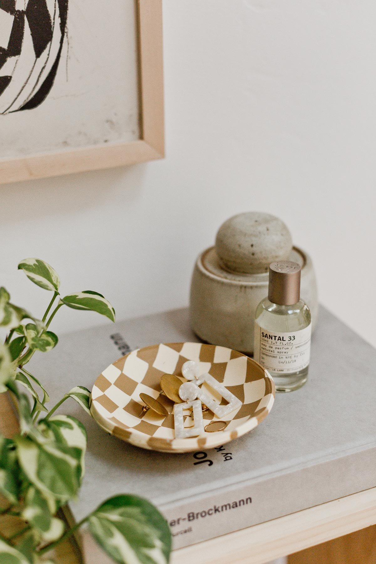 Checkered pattern clay bowl with earrings, resting on modern table.