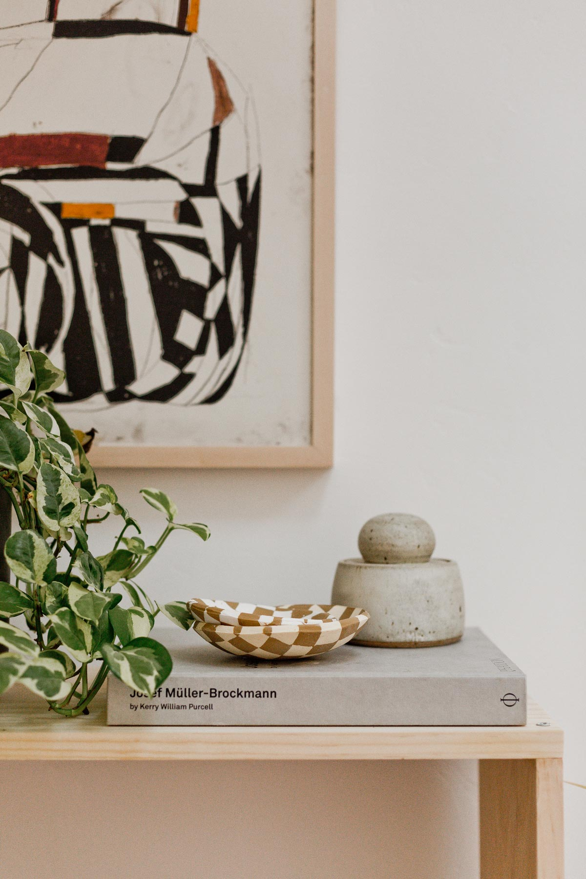 Modern, minimal table with abstract artwork and small objects.