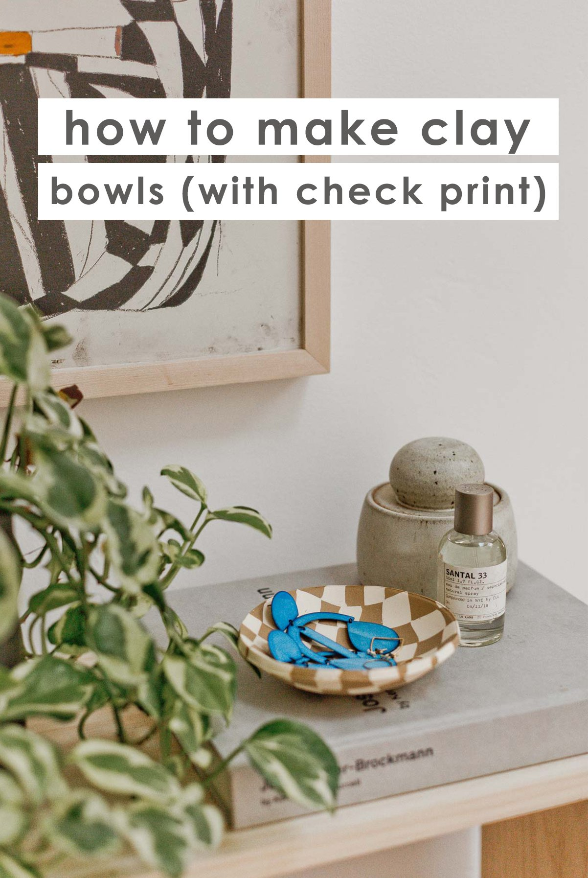 Check print clay bowl resting on book on top of modern table.