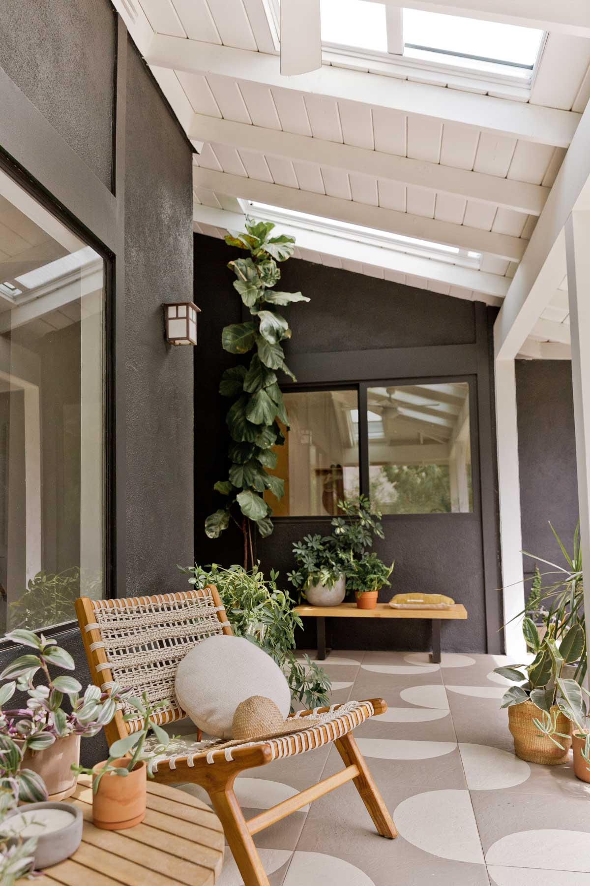 Modern black front porch with painted floor tiles and modern furniture.