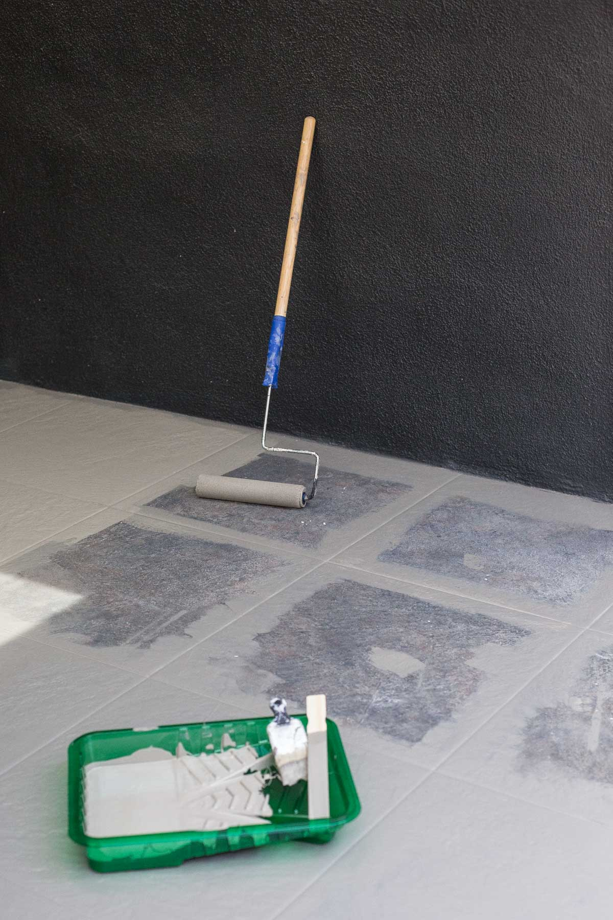 Painting tile floors with a pant roller and brush.
