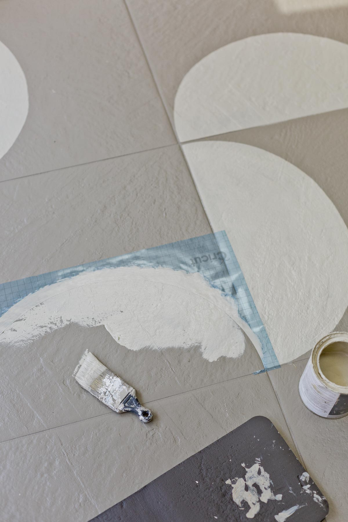 Painting floor tiles with a stencil and paint brush.
