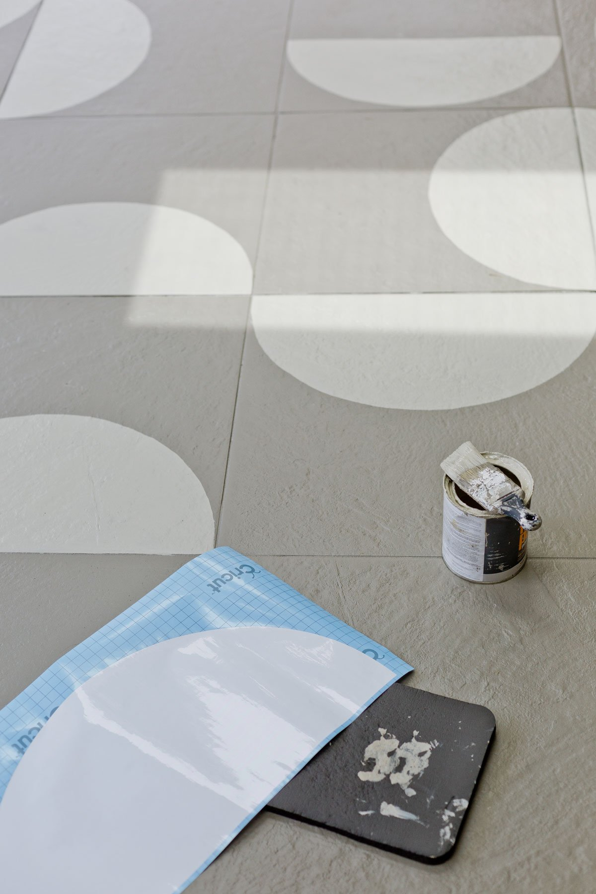 Painting floor tiles with a paint brush and custom made stencil.