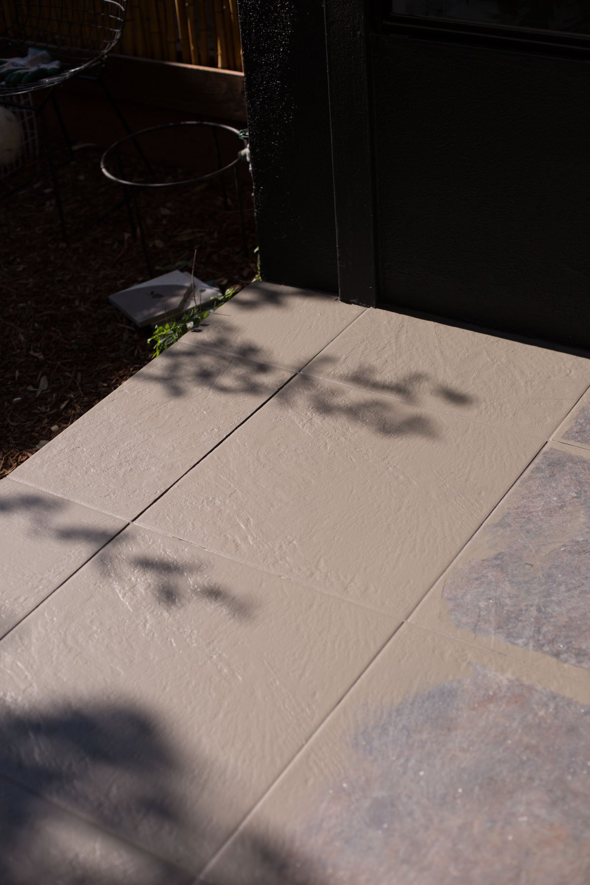 Painting floor tiles grey on a front porch.